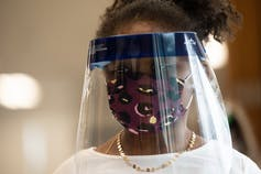 A young black girl wears a mask and a face shield over her face.