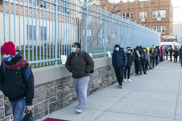 Grade school students line up to walk to school.