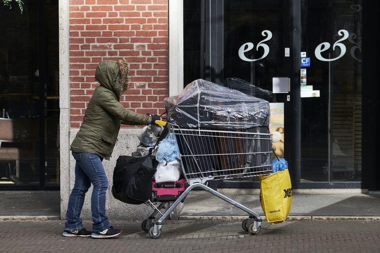 Woman in heavy winter coat pushes a full shopping car