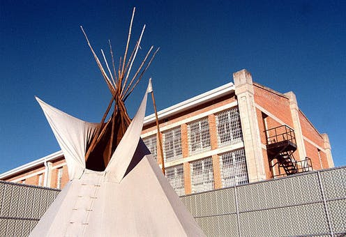 Tipi outside in front of a building.