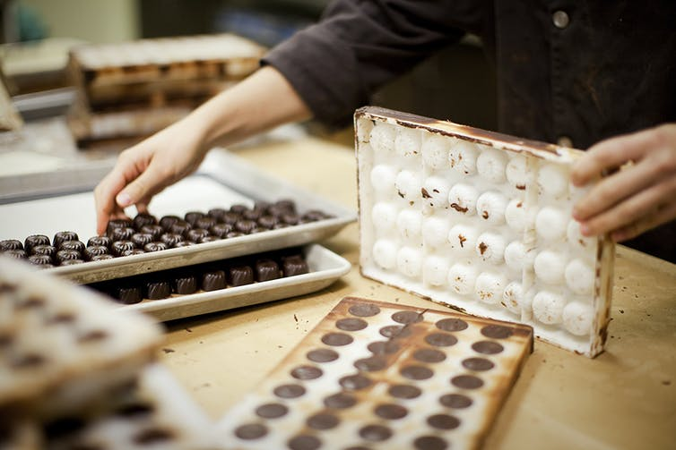a chocolate maker's hands remove finished candies from a chocolate mold