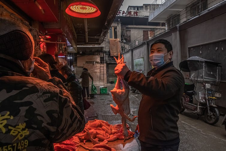Man wearing face mask at a market in Wuhan