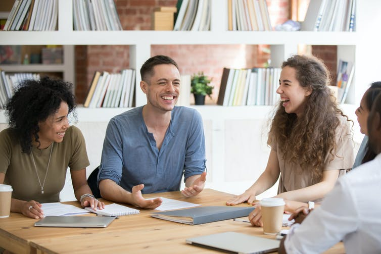 group of young academics laughing and chatting