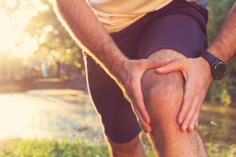 Runner holding a sore knee.