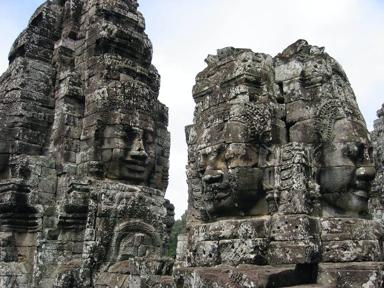 Human faces carved into stone towers of an Angkor temple