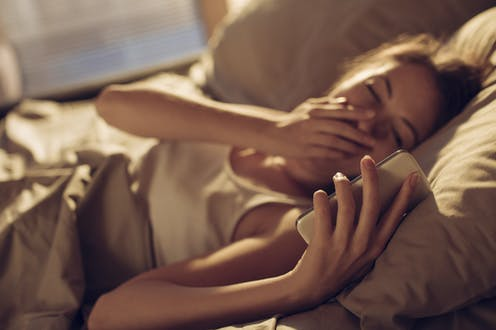 Woman lying in bed yawning and looking at phone