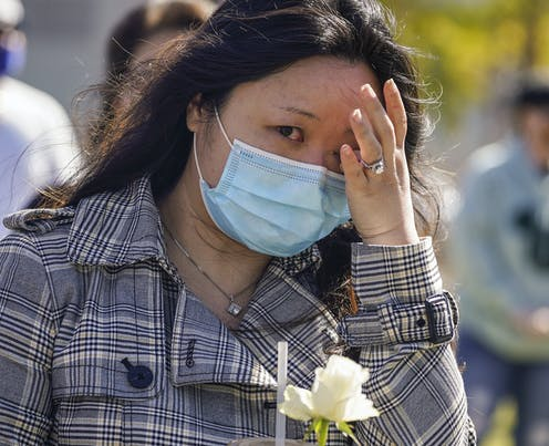 An Asian woman in a face mask with a white flower wiping a tear from her eye
