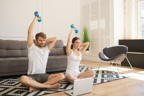 Man and woman sit doing at home workout