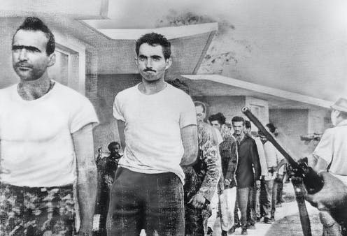 Grim-faced men march under the eye of armed Cuban guards.