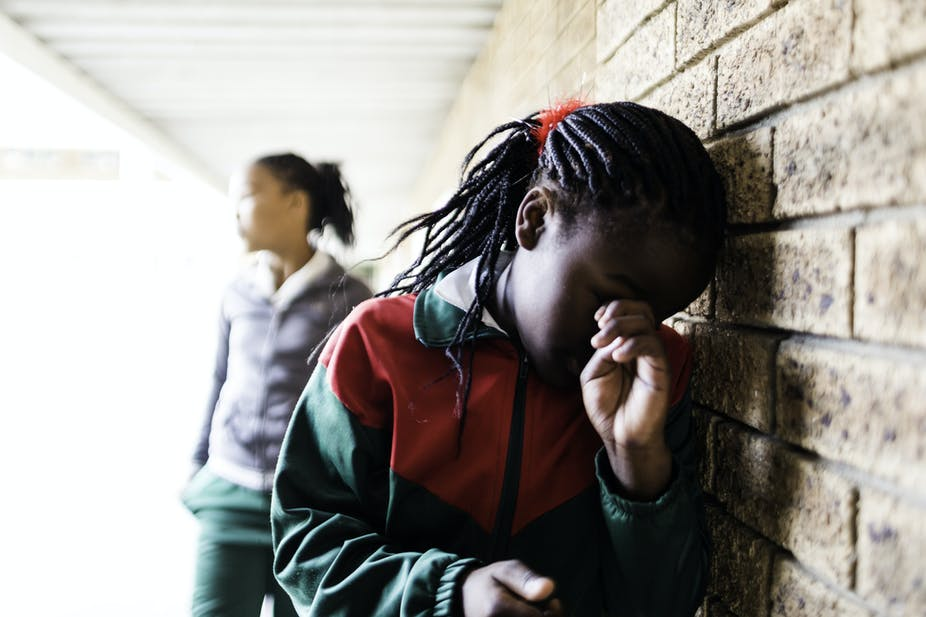 A girl wearing school uniform stands leaning against a wall crying.