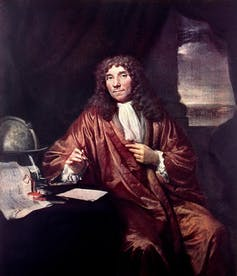 An oil painting of man with long curly hair holding a pair of tweezers posed next to a globe.