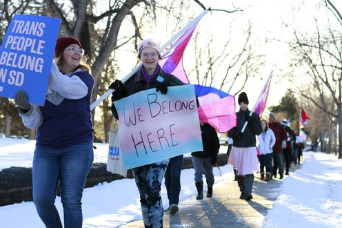 Youth march carrying transgender flags and signs