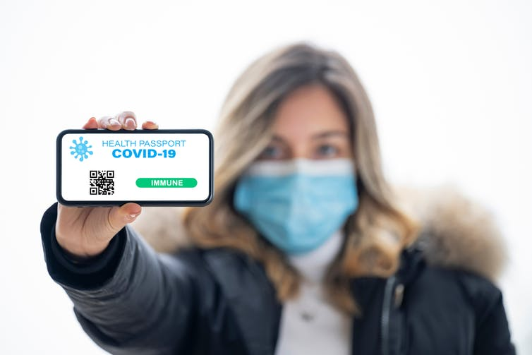 Woman with mask holding up vaccine passport on phone