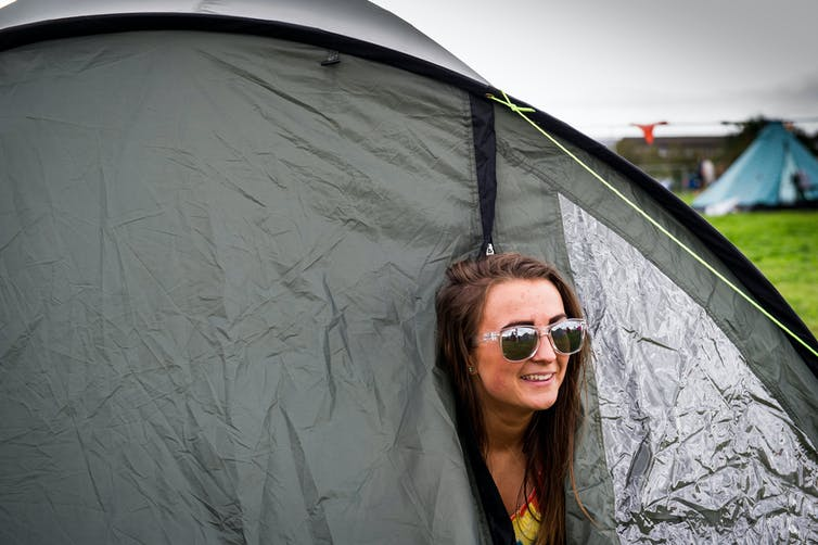 Festival girl poking her head out of a tent