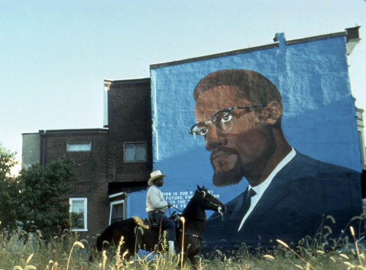 A man rides a horse in front of a mural of Malcolm X.