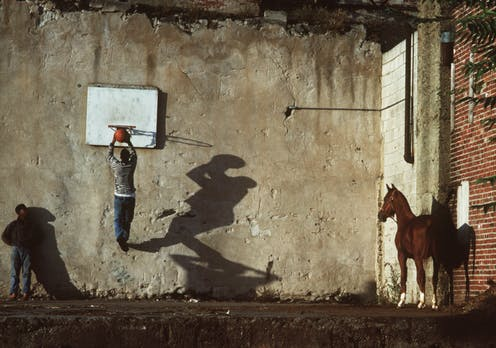 Two boys play basketball as a horse looks on.