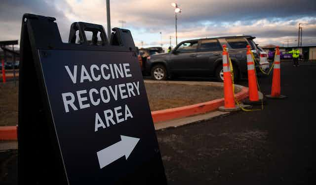 A sign shows the way to a vaccine recovery area.