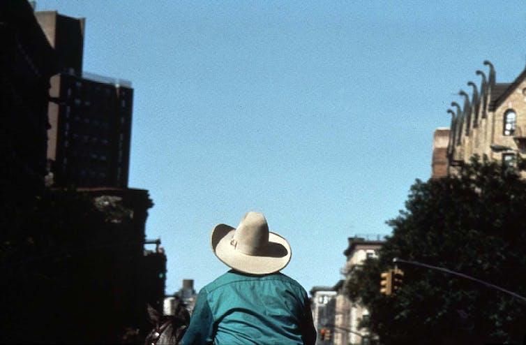 A man wearing a white cowboy hat rides a horse through a city street.