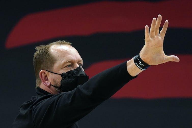 Toronto Raptors head coach Nick Nurse, wearing a mask, raises his hand as he calls a play