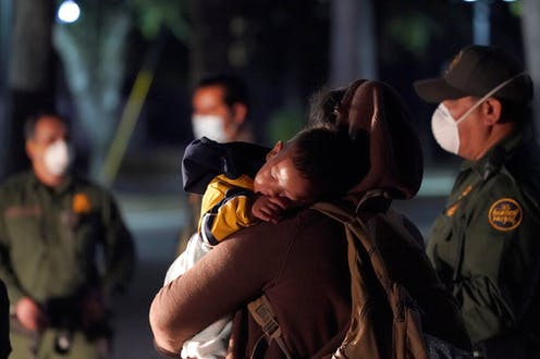 A migrant child sleeps on the shoulder of a woman at an intake area after turning themselves in upon crossing the U.S.-Mexico border, with U.S. border patrol agents standing around them.