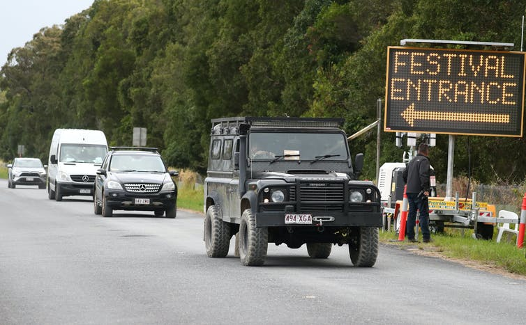 Cars drive away from a sign saying 'festival entrance'.