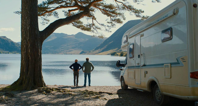 Two men stand by lake with campervan.