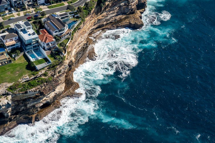 Homes atop ocean cliff face