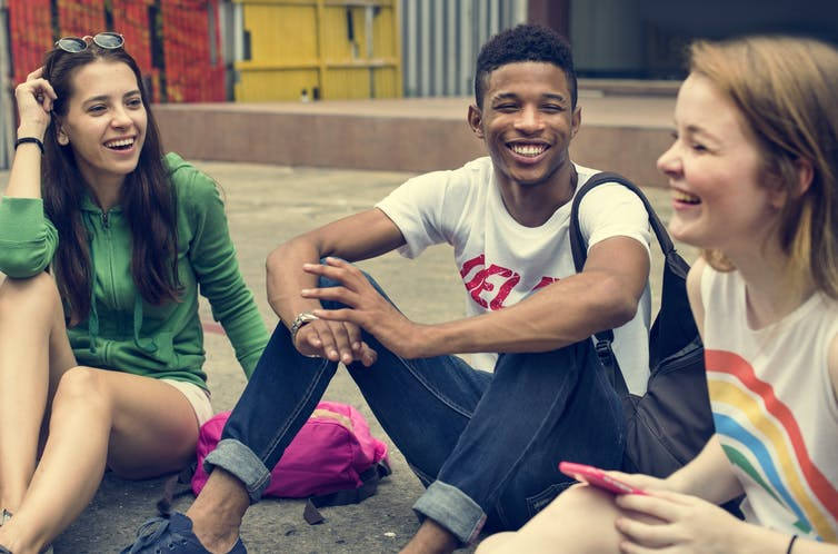 Group of young friends laughing about something.