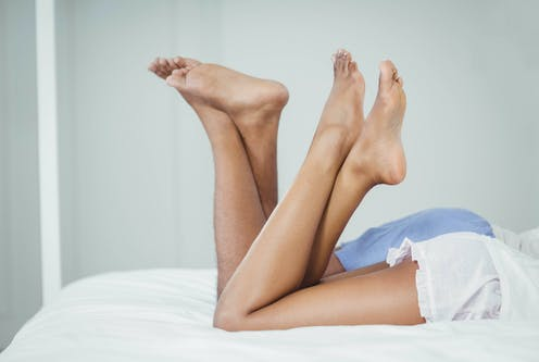 Two intertwined legs in bed