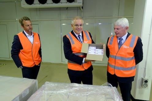 Prime Minister Scott Morrison holding a box full of COVID-19 vaccines