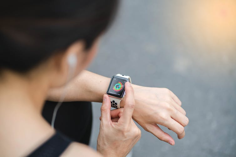 A woman controls her Apple watch.