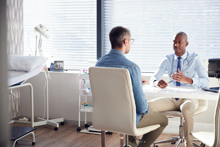 A man consults with a doctor in a bright office.