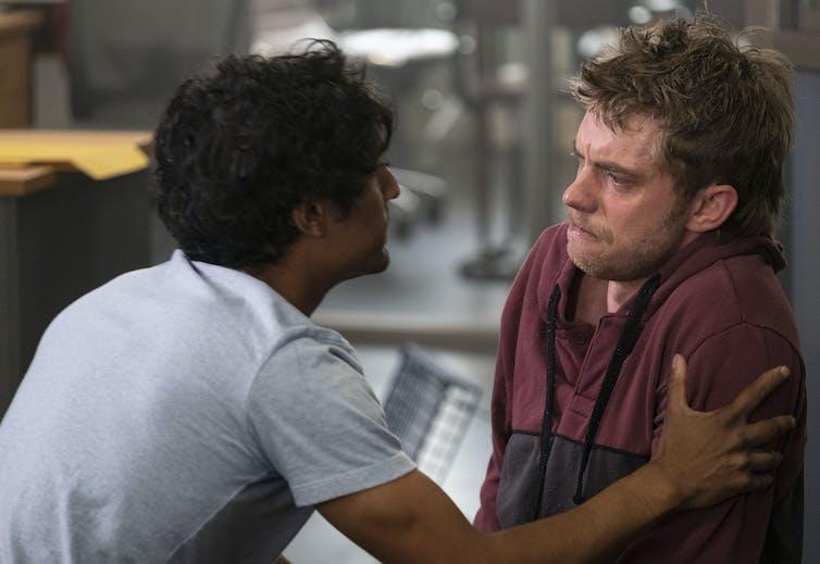Two men in intense emotional embrace