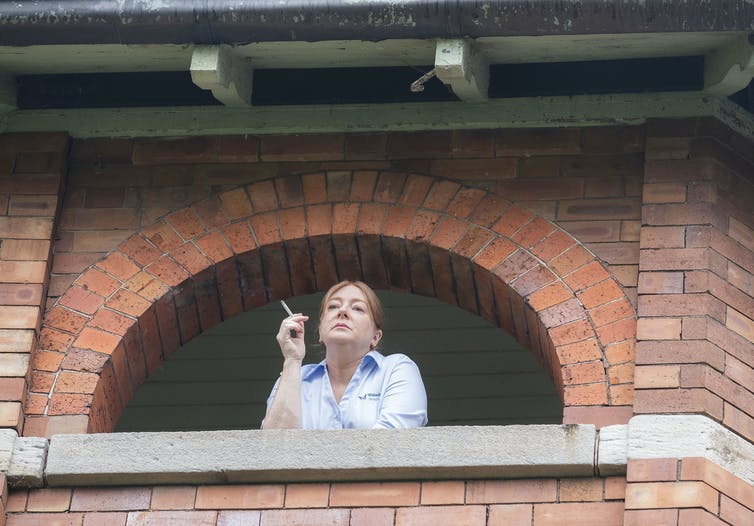 Woman smokes on balcony.