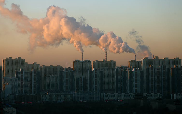Smoke billows from a coal-fired powered station behind a city skyline.