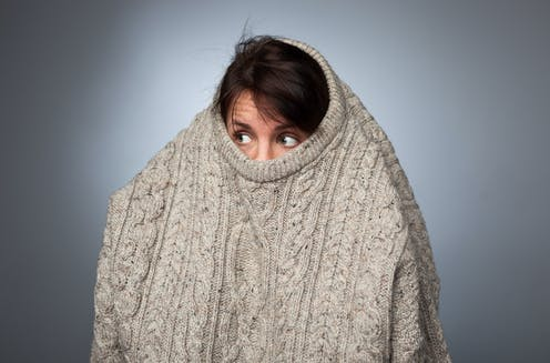 A woman hides within a big jumper looking slightly scared