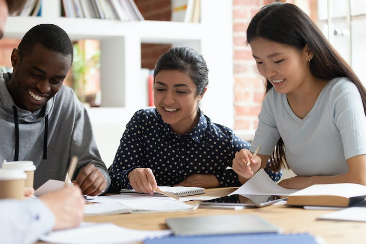 Black, South Asian and East Asian students laughing while studying together