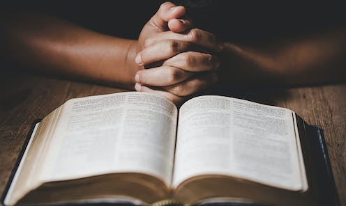 Praying hands in front of an open Bible.