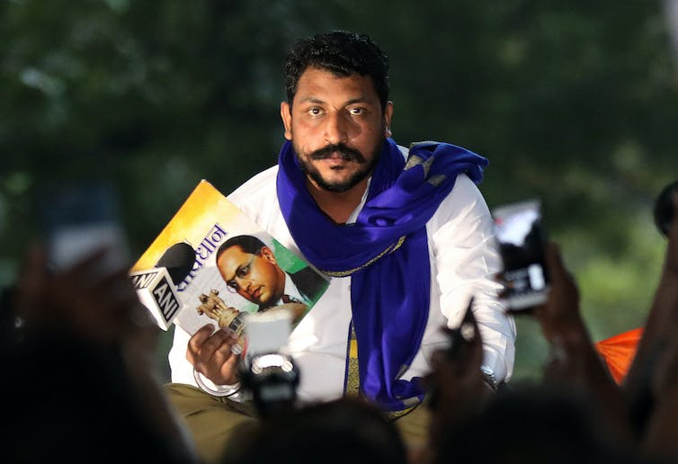 Indian man with moustache and scarf holding political posters at a protest rally in Delhi October 2020.