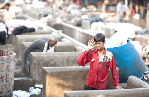 A young Dhobi at work at the Dhobi Ghat, in Mumbai India. The Dhobi are an caste group found in Pakistan and India who specialize in washing clothes.
