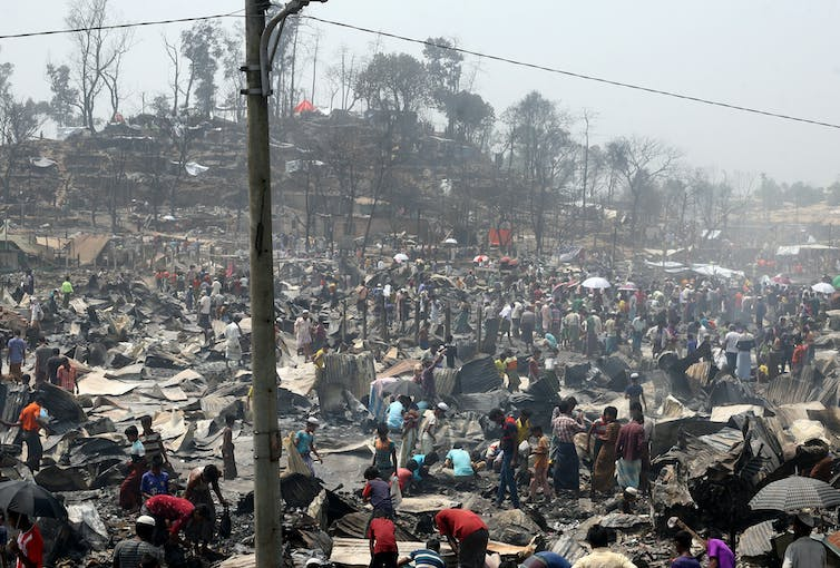 People looking through burned structures.