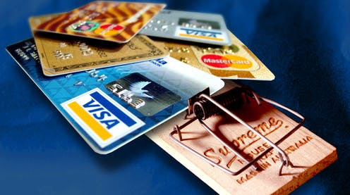 Several credit cards laid out on a mouse trap.