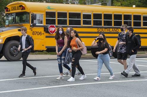 Students walk near a bus.