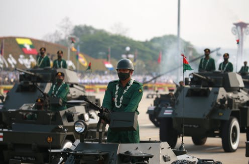 Soldiers drive tanks bearing Myanmar flags down a public street