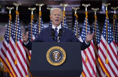 President Joe Biden holds his hands out wide as he gives a speech at a lectern with a row of American flags behind him.