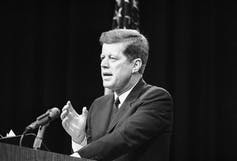 President John F. Kennedy gestures with his right hand as he speaks in front of a lectern in 1962.