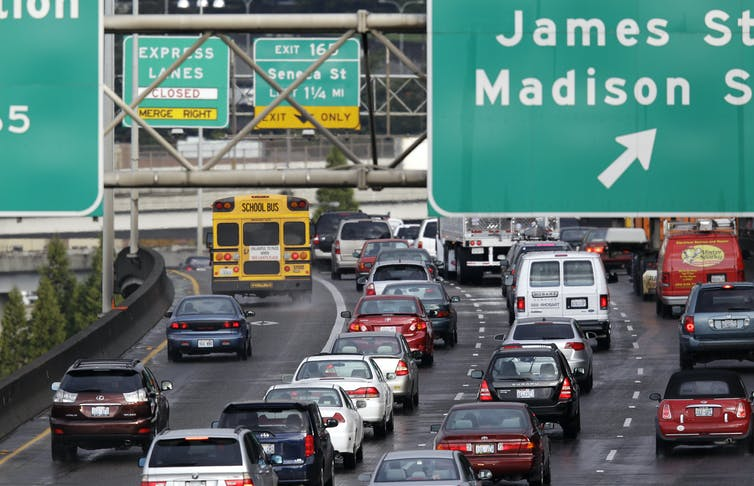 Heavy traffic moves along an interstate highway in Seattle with large signs directing cars to various offramps