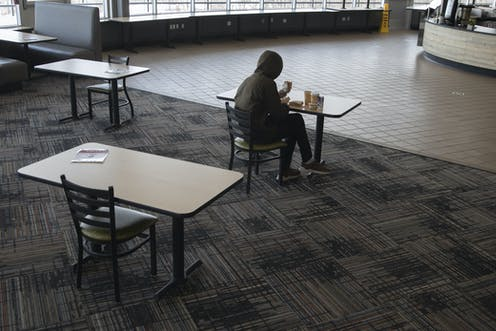 A student sits alone in a university cafeteria.