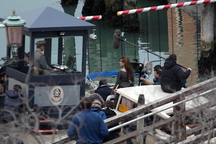Angelina Jolie in a boat in a Venice canal, surrounded by crew members