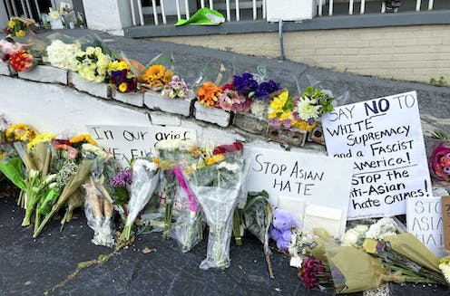 Flower bouquets and signs demonstrate grief and outrage at the killings in Atlanta